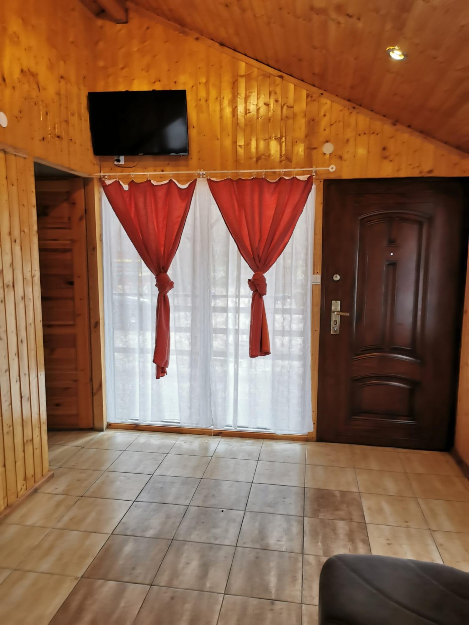 Zdjęcie wnętrza domku PREMIUM. Zdjęcie przestawia duży pokój z telewizorem.